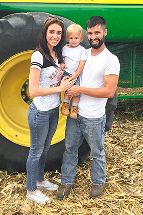 Matt Hostettler and his family in front of a combine